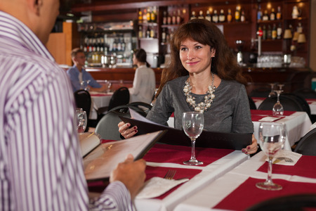 Photo pour Smiling young woman visiting restaurant with her husband, discussing menu at table - image libre de droit
