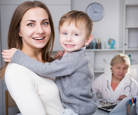 Foto de Woman is satisfied of medical examinaing of her son in clinic. - Imagen libre de derechos