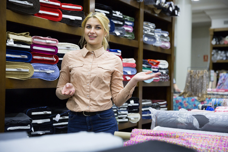 Photo for Competent young saleswoman offering various interesting cloth in textile shop - Royalty Free Image
