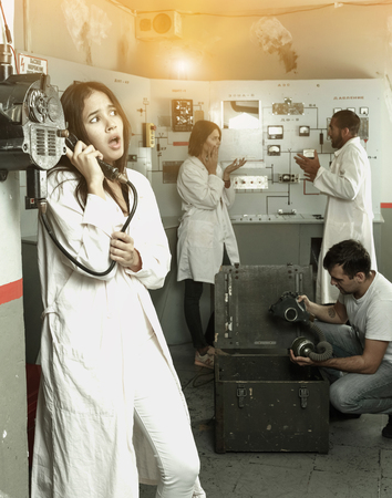 Foto de Young upset girl talking on old telephone while visiting with friends quest room in view as closed nuclear bunker - Imagen libre de derechos