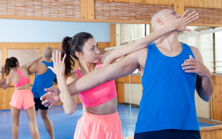 Photo pour Woman is training with man on the self-defense course in gym - image libre de droit