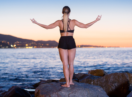 Photo pour Female 24-31 years old is practicing stretching on a rock near sea at the dawn. - image libre de droit
