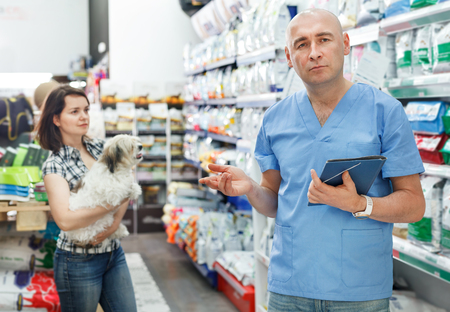 Foto für Man veterinarian with folder standing near shelfs with dry food in a pet store - Lizenzfreies Bild