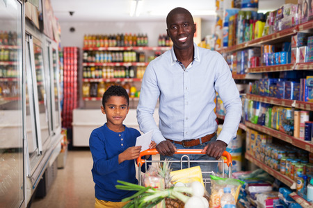 Foto de Portrait of friendly African American father and son with purchases during family shopping in store - Imagen libre de derechos