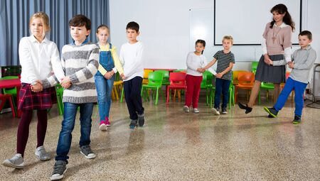 Foto de Group of cheerful school kids learning to dance in pairs with their teacher in classroom on recess - Imagen libre de derechos