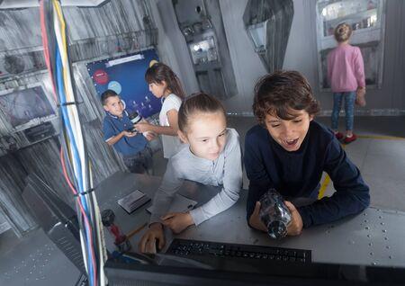 Foto de Focused boys and girls look for a way out in quest room bunker - Imagen libre de derechos