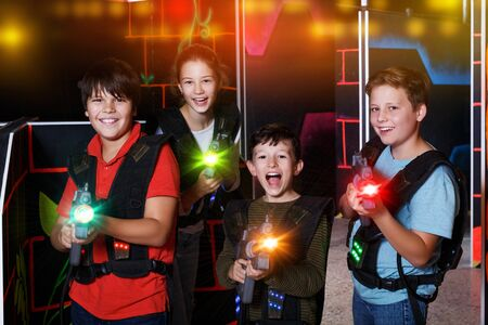 Photo pour Portrait of happy excited teen kids with laser guns during lasertag game in dark room - image libre de droit