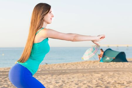 Photo for Portrait of sportswoman which is doing excercises for warm-up on the beach near sea. - Royalty Free Image