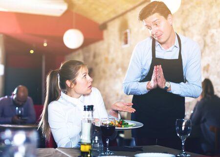 Foto de Female client expressing displeasure with food talking to excusing waiter. Focus on woman - Imagen libre de derechos