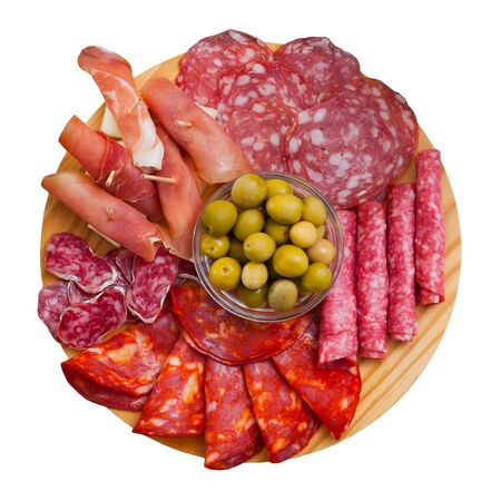 Photo for Top view of coldcuts of delicious Spanish cured jamon and piquant sausages garnished with green olives on wooden board. Isolated over white background - Royalty Free Image