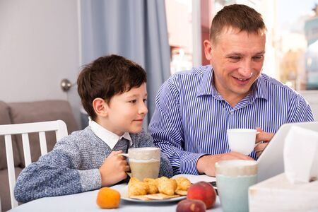 Photo pour Happy tween boy spending time with his father at home, drinking tea with sweets and using laptop - image libre de droit
