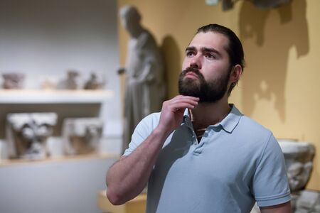Foto de Man visiting sculpture hall in historical museum and looking at exhibits - Imagen libre de derechos