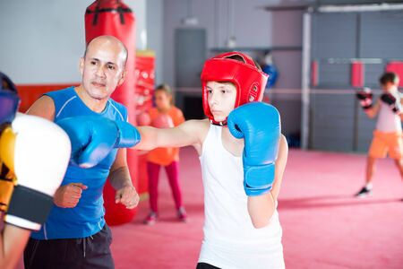 Photo for Boxing instructor controls the sparring between the two boys in the gym - Royalty Free Image