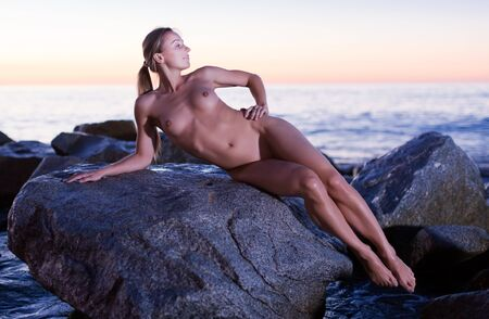 Photo for Nude young happy woman is lying on a rock near the sea at the dawn. - Royalty Free Image