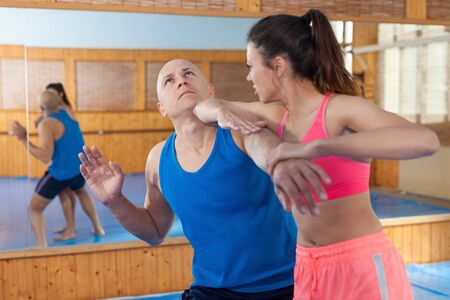 Photo pour Active woman with professional trainer are training captures on the self-defense course in gym - image libre de droit