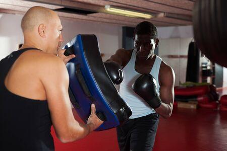 Photo pour Men practicing effective techniques of self-defence during individual class in training room - image libre de droit