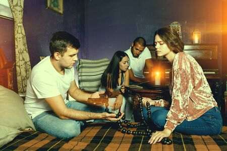 Foto de Young friends looking at wooden rosary while solving conundrum as detectives in quest room with old furnitures - Imagen libre de derechos