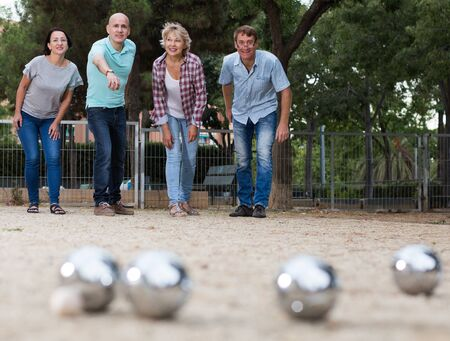 Photo pour Smiling mature people playing petanque on sand together - image libre de droit