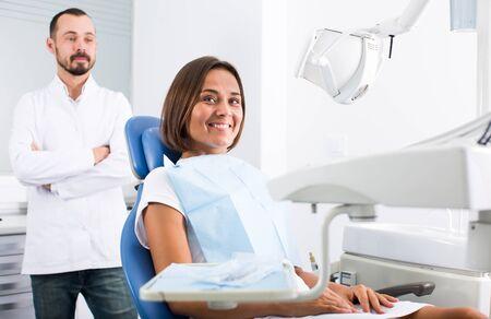 Foto de Girl is sitting satisfied in chair after treatment in dental office - Imagen libre de derechos
