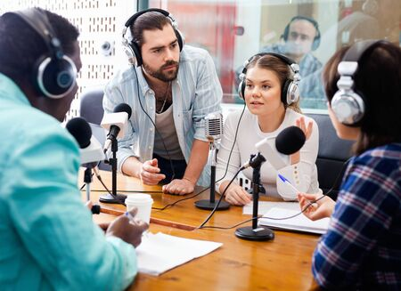Photo for Scandal interview. Two young  outraged guests answering provocative questions of cheerful  friendly  radio hosts  during live radio show - Royalty Free Image
