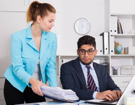 Photo for Businesswoman bringing to unhappy male coworker big pile of files - Royalty Free Image