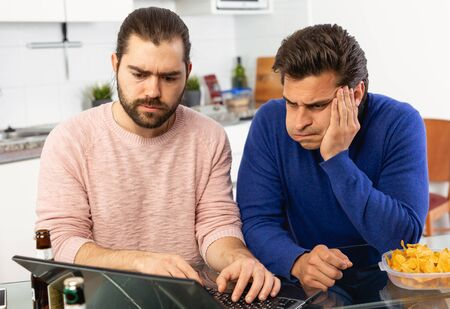 Photo pour Friendly male meeting over beer at home, men looking at laptop and discussing - image libre de droit