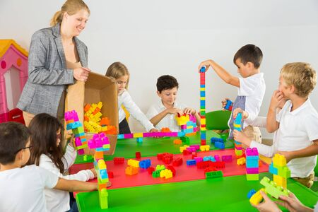 Foto de Happy kids and female teacher playing together with colorful toy building blocks in classroom at elementary school - Imagen libre de derechos