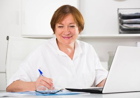 Photo pour Senior female worker working productively on project in office - image libre de droit