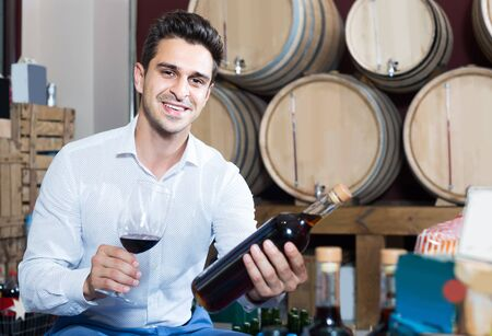 Foto de portrait of smiling man holding bottle and glass of wine in alcohol section with woods - Imagen libre de derechos