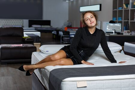 Photo for Sensual positive woman in black clothes posing on bed with new mattress in furnishing salon - Royalty Free Image