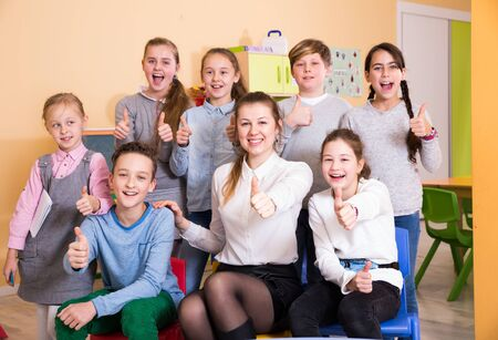 Foto de Cheerful group of pupils with female teacher posing together in schoolroom, giving thumbs up - Imagen libre de derechos