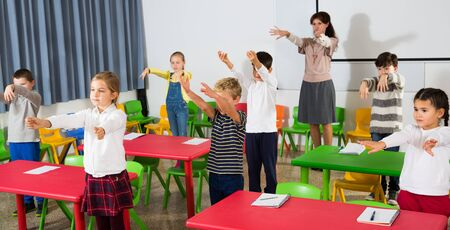 Foto de Focused pupils doing little warm-up in class with teacher at lesson in elementary school - Imagen libre de derechos