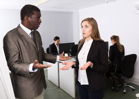 Photo for Irritated boss scolding female subordinate in modern office, pointing out shortcomings in work - Royalty Free Image