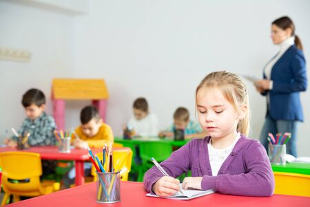 Foto de Portrait of little assiduous girl with pen and notebook at lesson in elementary school - Imagen libre de derechos