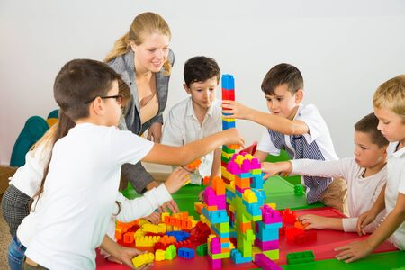 Foto de Young female teacher and happy schoolkids building castle from plastic toy blocks during lesson in classroom - Imagen libre de derechos