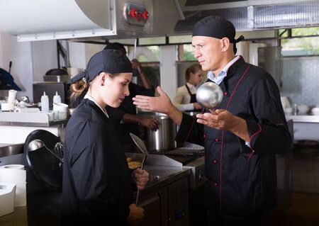 Photo for Angry male chef talking to his female assistant in commercial kitchen - Royalty Free Image