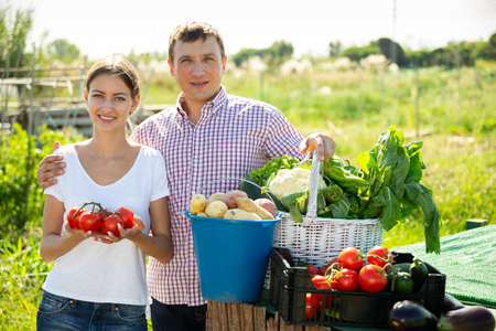 Photo pour Young family couple with harvest of vegetables in garden outdoor - image libre de droit