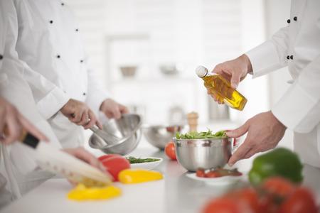 Foto de anonymous hands preparing food in professional kitchen - Imagen libre de derechos