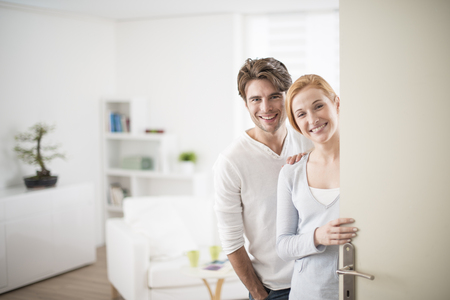 Photo pour Cheerful couple inviting people to enter in home - image libre de droit