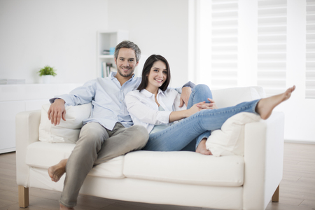 Photo pour Couple at home relaxing in sofa - image libre de droit