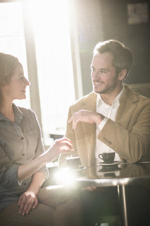 Photo pour handsome couple talking and drinking coffee in a bar - image libre de droit