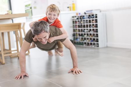 Foto de father and son  are doing pushups and having fun  at home - Imagen libre de derechos