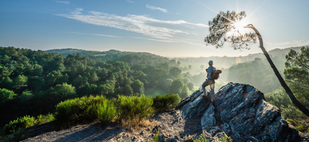 Photo pour A walker on a mountain trail, looking down the valley at sunrise - image libre de droit