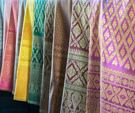 Photo for Beautiful Row of Traditional Colorful Thai Silk Fabric Textile with Seamless Pattern of Vintage Thai Design Style hanging in The Fashion Store for Sell used as Template - Royalty Free Image
