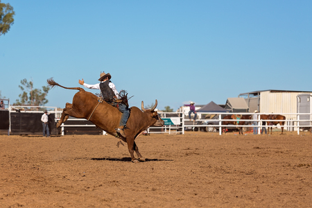 Foto de A cowboy competing in a bull riding event at an Australian country rodeo - Imagen libre de derechos