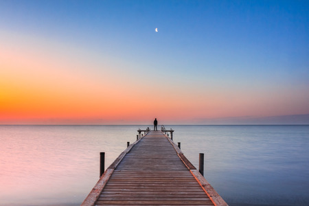 Photo pour A man standing at the end of a jetty watching the moon at sunrise - image libre de droit