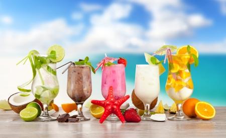 Foto de Summer cocktails with pieces of fruit on wooden table. Blur beach on background - Imagen libre de derechos