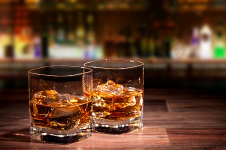 Whiskey drinks on wooden table with blur bar on background