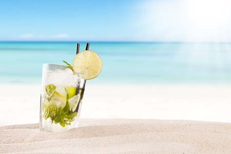 Photo for Exotic summer drink in sand, blur beach on background - Royalty Free Image