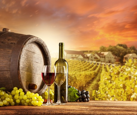 Photo for Old wooden keg with bottle and glass of red, white wine  Rural vineyard on background - Royalty Free Image